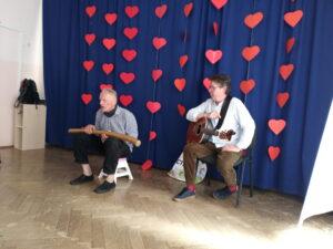 dwóch mężczyzn siedzi na tle kotary z instrumentami na kolanach