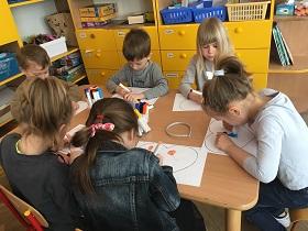 Przy stoliku siedzi szóstka dzieci, trzymająca w rękach flamastry. Na stoliku znajdują się serca z papieru.