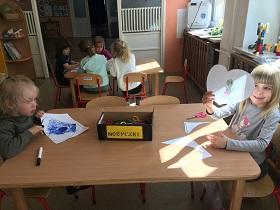 Na pierwszym planie znajduję się dwójka dzieci, siedząca przy stoliku i trzymająca w rękach nożyczki i kartkę papieru. Na stoliku znajduję się pudełko z napisem nożyczki. W dalszym planie widać czwórkę dzieci siedzącą przy stoliku.