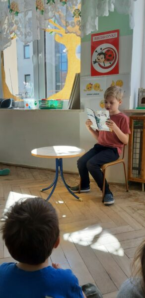 Na krzesełku siedzi chłopiec, w dłoniach trzyma książkę, przed nim siedzą na podłodze dzieci.