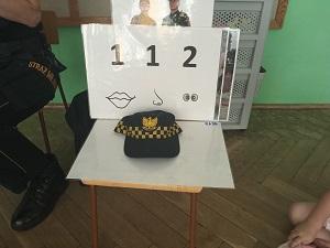 Na stoliku leży czapka strażnika miejskiego, w tyle jest biała plansza z numerem alarmowym 112