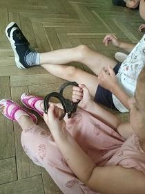 Dzieci siedzą na podłodze, dziewczynka trzyma w rękach kajdanki.