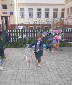 Dzieci znajdują się na dworze i robią duże bańki wodne