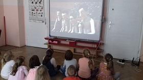 Dzieci znajdują się na podłodze. Twarze mają zwrócone do tablicy interaktywnej, na której wyświetlany jest film. Na ekranie widać cztery postacie męskie.