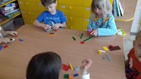 Dzieci konstruują budowlę z klocków LEGO przy stołach. Przed każdym dzieckiem leży zestaw klocków.