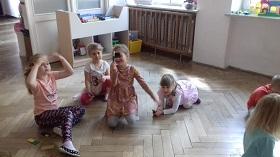 Dzieci znajdują się w sali na podłodze. Dziewczynka pokazuje swoją budowlę. Reszta dzieci patrzy.