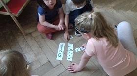 Dzieci siedzą na podłodze i układają wyraz szacunek z pojedynczych liter