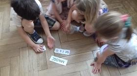 Dzieci siedzą na podłodze i układają wyraz miłość z pojedynczych liter