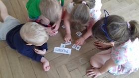 Dzieci siedzą na podłodze i układają wyraz piękno z pojedynczych liter