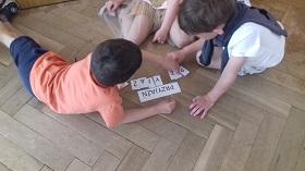 Dzieci siedzą na podłodze i układają wyraz przyjaźń z pojedynczych liter