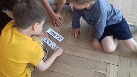 Dzieci siedzą na podłodze i układają wyraz dobroć z pojedynczych liter