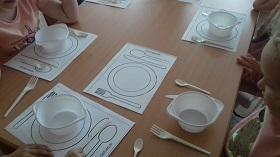 Na stoliku znajduję się kartki papieru z narysowanymi sztućcami i talerzem. Dodatkowo dzieci układają w odpowiednie miejsce na kartkach plastikowe naczynia i sztućce.
