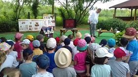 Mężczyzna opowiada o pszczołach na podstawie prezentacji wyświetlanej na ekranie telewizora. Dzieci siedzą zwrócone twarzami do niego.