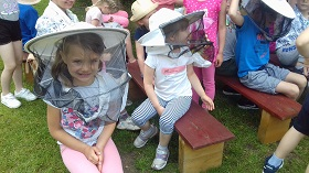 Na pierwszym planie siedzi trójka dzieci, która ma nałożony biały kapelusz pszczelarski.