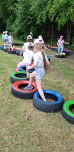 dzieci pokonują tor przeszkód z opon