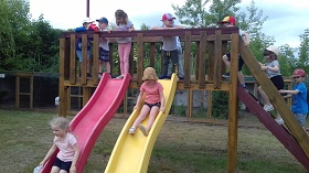 Dzieci stoją na drewnianej zabawce, czekając na swoją kolej by zjechać na zjeżdżalni. Dwoje dzieci zjeżdża na zjeżdżalni.