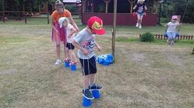 Pani w pomarańczowej bluzce, pokazuje dwójce dzieciom jak chodzić na szczudłach.
