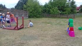 Dziecko naciąga liny i strzela piłką w stronę ustawionych w wieżę wiader.