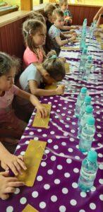 dzieci wykonują świeczki z wosku pszczelego