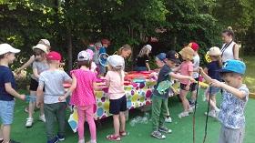 Dzieci stoją przy dużym, prostokątnym stole. Mają w rękach szablony i robią bańki mydlane.