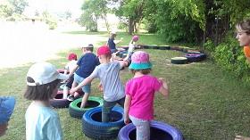 Dzieci pokonują tor przeszkód ułożony z kolorowych opon.