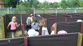 Dzieci znajdują się w środku brązowego labiryntu i szukają wyjścia.