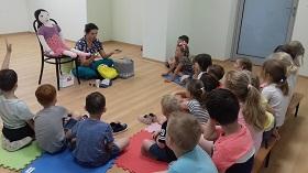 Dzieci siedzą na matach i ławeczkach. Są zwrócone w kierunku pani. Pani pokazuje im produkty z plecaka.