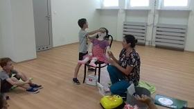 Chłopiec opatruje lalce guza nabitego na czole. Obok siedzi pani