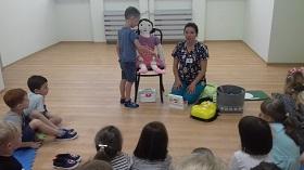 Chłopiec opatruje lalce nogę. Pani jest zwrócona do dzieci