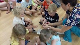 Pani pokazuje dzieciom jak należy opatrzyć ranę na dłoni.