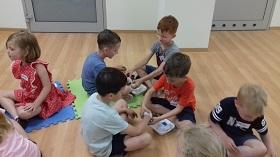 Dzieci w parach opatrują sobie rany na rękach, naklejając plaster i zakładając bandaż