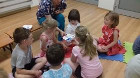 Pani rozdaje dzieciom pojemniki z artykułami pierwszej pomocy.