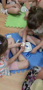 dziewczynki ćwiczą zakładanie opatrunku