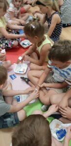 dzieci siedzą na podłodze i ćwiczą zakładanie opatrunku