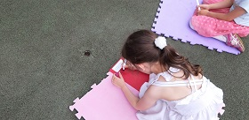 Na macie klęczy dziewczynka, mazakiem pisze swoje imię.