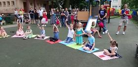 Dzieci siedzą na matach, podnoszą ręce do góry.