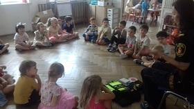 Dzieci siedzą na podłodze w sali. Patrzą w kierunku Pani, która jest strażnikiem miejskim