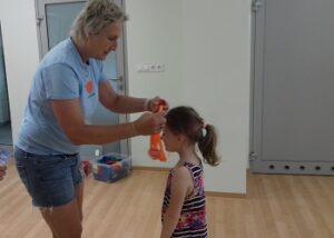 Pani zakłada dziewczynce pomarańczowy medal na szyję