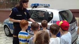 Pani strażnik otwiera dzieciom drzwi wozu. Napis straż miejska