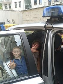 Chłopiec siedzi wewnątrz auta i macha