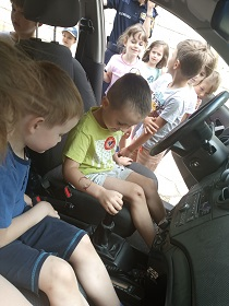 Dwóch chłopców siedzi w samochodzie Straży Miejskiej i oglądają jego wnętrze. Obok auta stoją dzieci.
