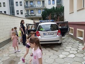 Na parkingu przedszkola stoi samochód Straży Miejskiej, przy nim stoi Pani strażniczka miejska oraz dzieci, które oglądają auto.