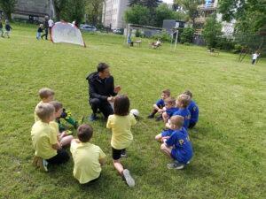 dzieic siedzą na trawniku i słuchają trenera