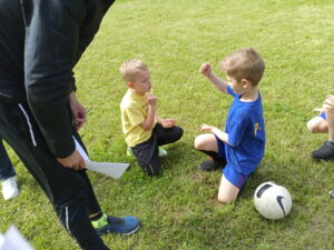 dzieci na trawie grają w kamień, papier, nożyczki