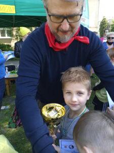 dzieci i mężczyzna trzymają medal