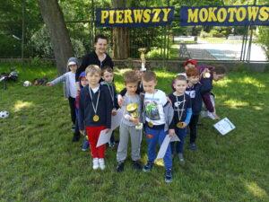 dzieci stoją na trawie z medalami i pucharem