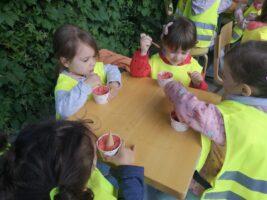 dzieci w kamizelkach przy stolikach jedzą lody