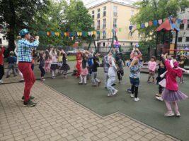 dzieci tańczą do muzyki przed wodzirejem