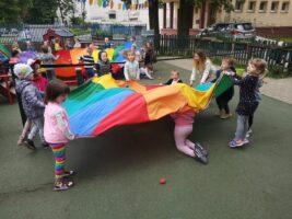 dzieci w ogrodzie bawią się chustą animacyjną