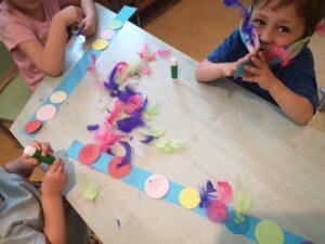 dzieci przy stole ozdabiają pióropusze